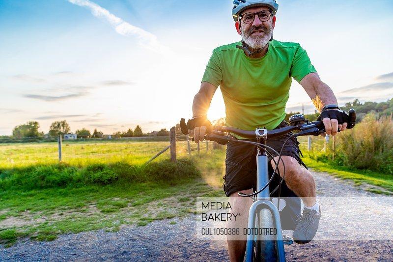 Mature man mountain biking in countryside