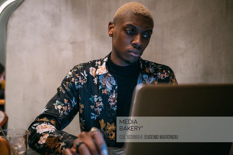 Stylish man using laptop, concrete wall background