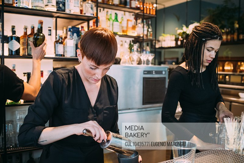 Two young women wearing black clothes standing behind bar counter, preparing drinks.