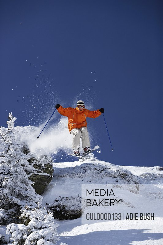 male skier jumping over mound past trees on slope