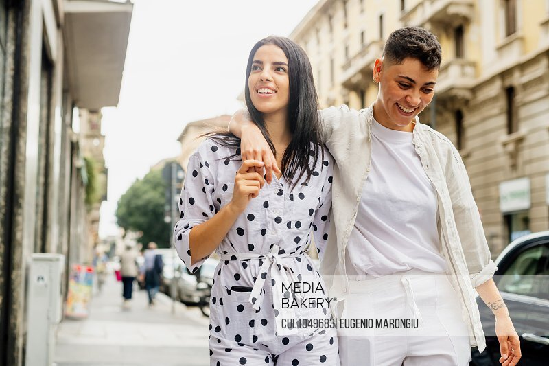 Young lesbian couple walking arm in arm down a street.