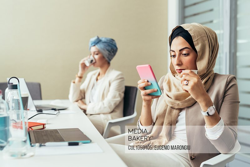 Businesswoman in office, using phone