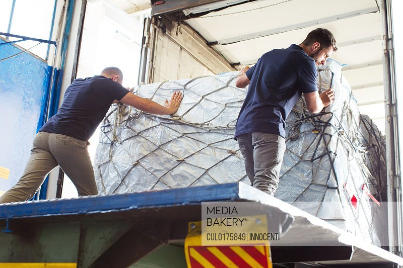 Workers pushing freight into air freight container