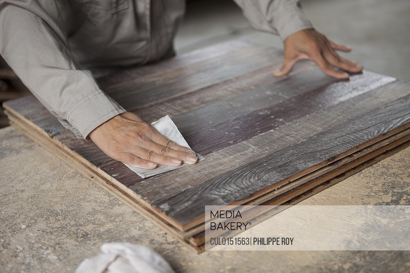 Carpenter smoothing surface of wood plank with sandpaper in factory Jiangsu China