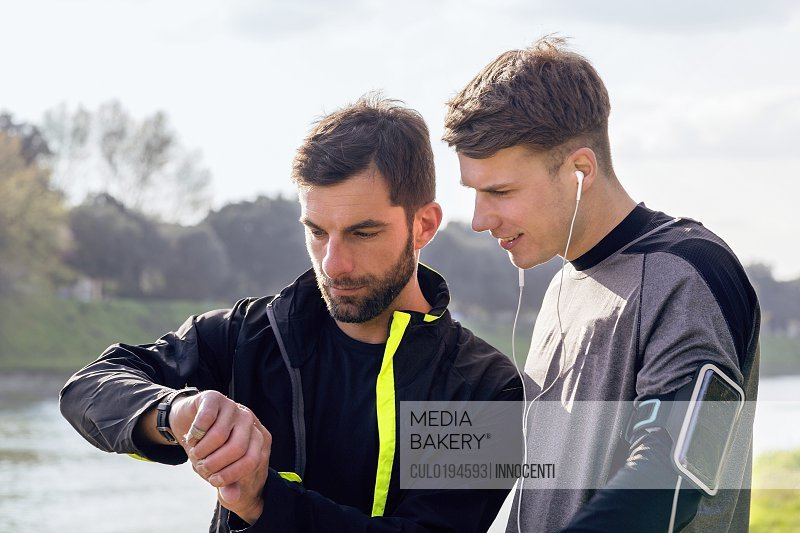 Two male friends outdoors ready to work out looking at activity tracker