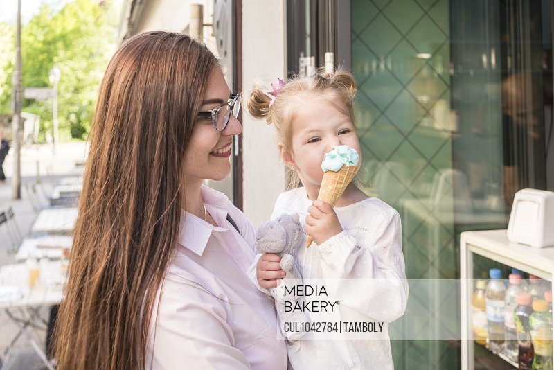 A mother standing outside a cafe holding her daughter as she eats an ice cream cone and holds a cuddly toy.