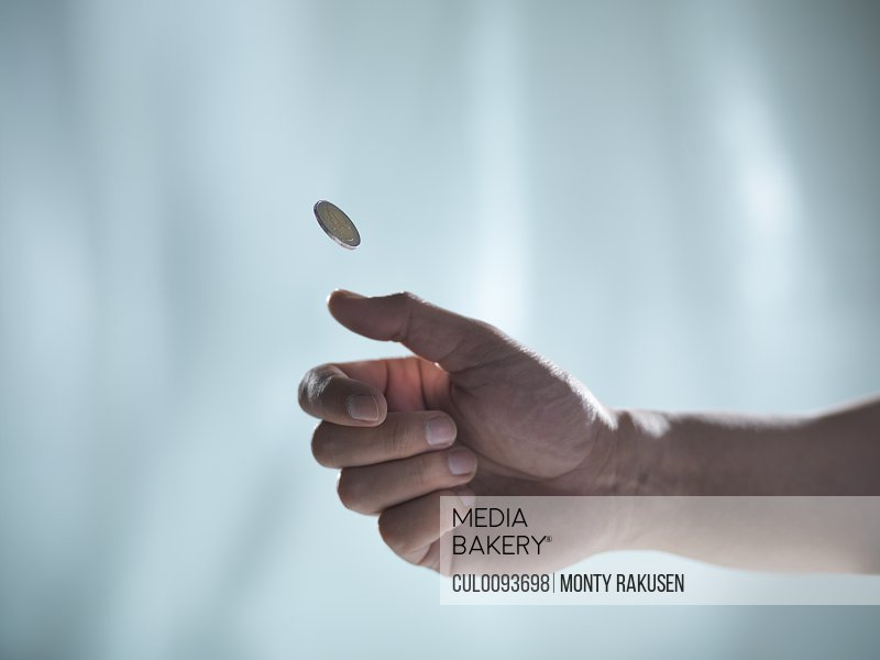 Close up of hand tossing coin