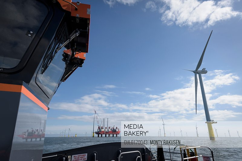 View of offshore wind farm and construction ship from boat