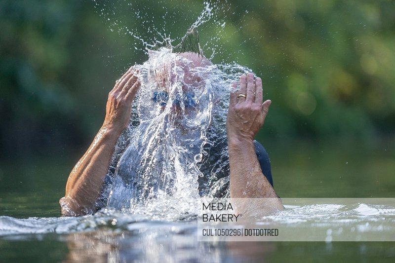 Swimmer in river, splashing water on face