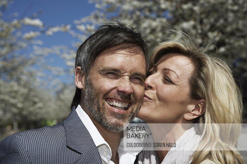 Woman kissing boyfriend outdoors