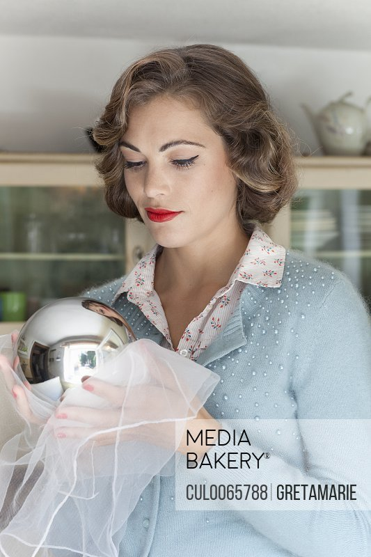 Woman polishing mirrored ball