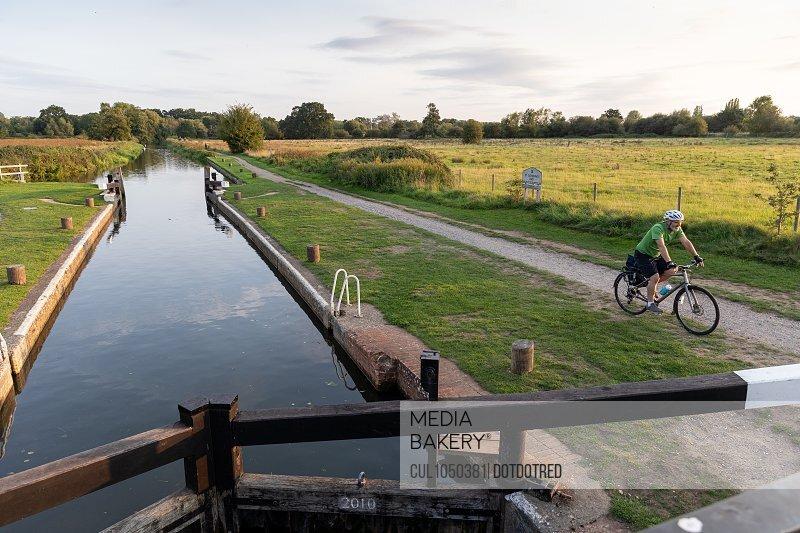 Man cycling beside canal lock