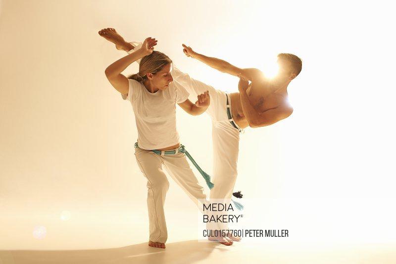 Mid adult couple practising capoeira
