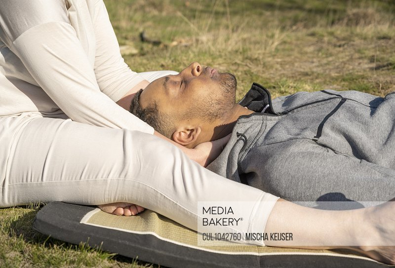 A young man receiving a neck massage from a masseur sitting on the ground by his head.