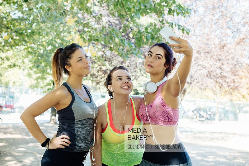 Friends exercising and taking selfie in park