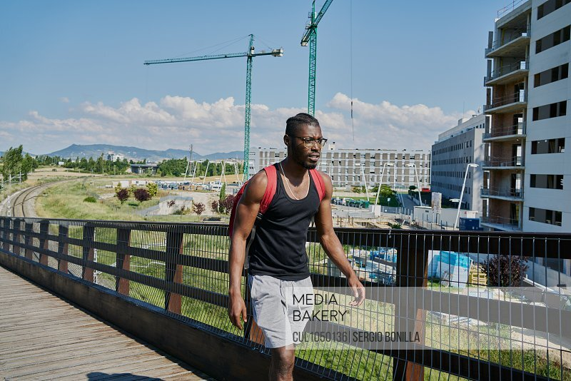 Young man walking over bridge