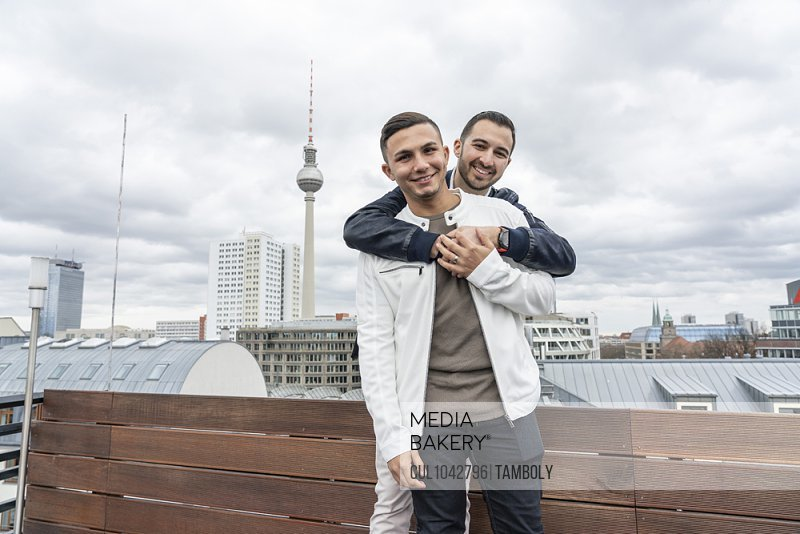 A homosexual male couple looking at the camera, hugging and enjoying a vacation in Berlin.