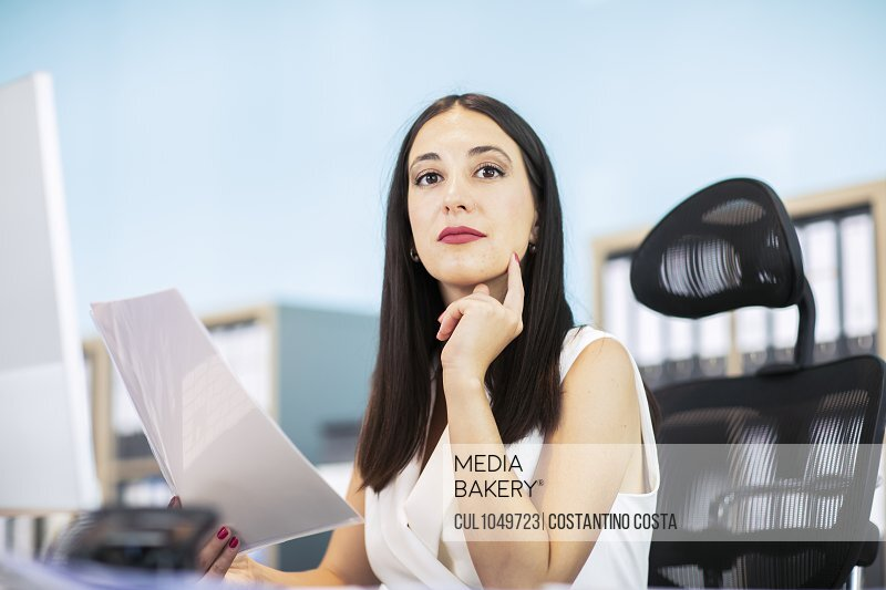 Business woman sitting at desk, holding document