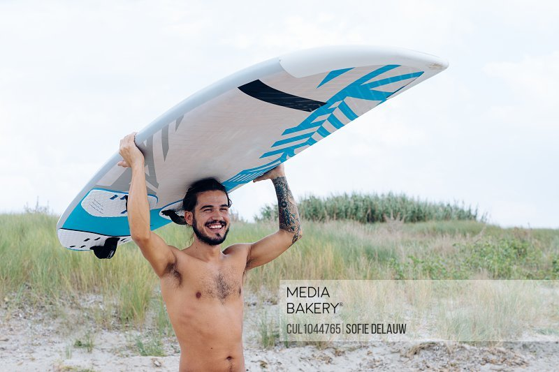 Surfer with surfboard by seaside