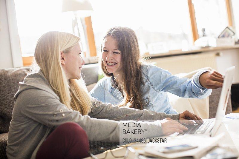 Teenage girls using laptop at home