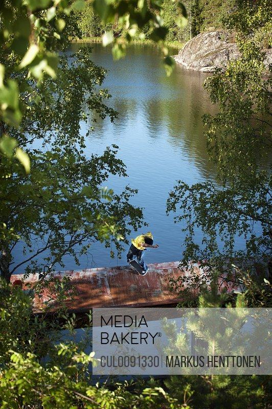 Boy standing on dock in lake