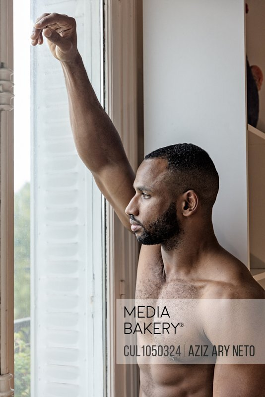 Bare chested man looking out of window