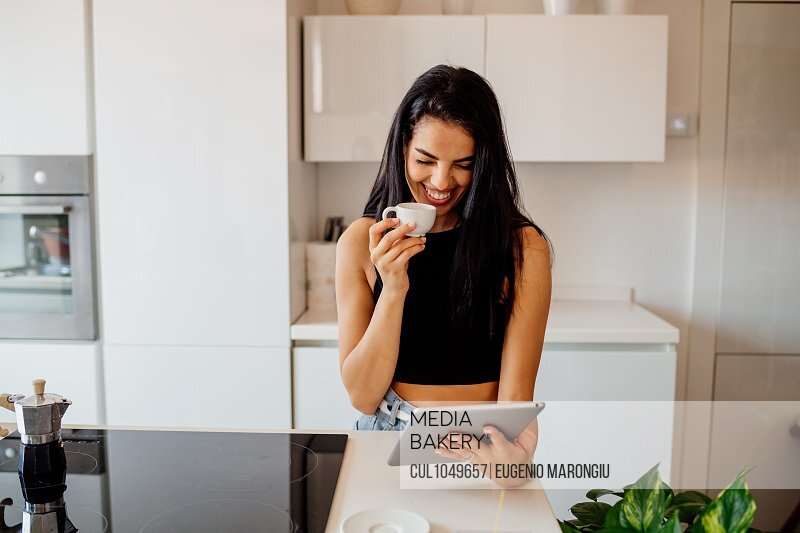Young woman with long brown hair standing in kitchen, looking at digital tablet.