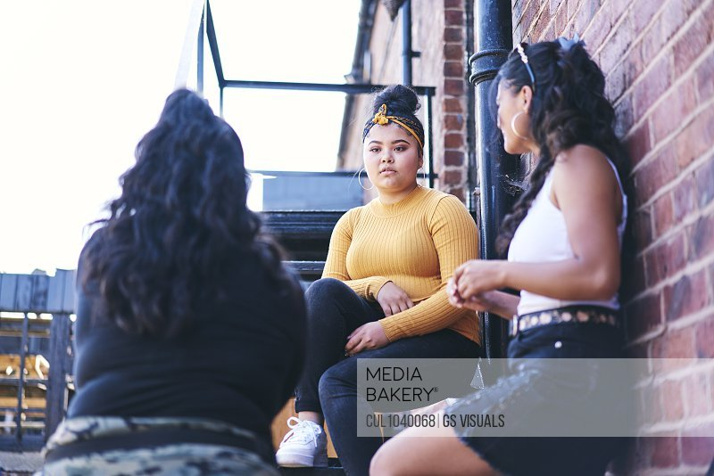 Young woman and her teenage sisters talking on fire escape