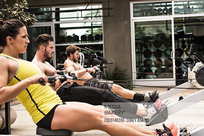 Bodybuilders on rowing machine outdoors