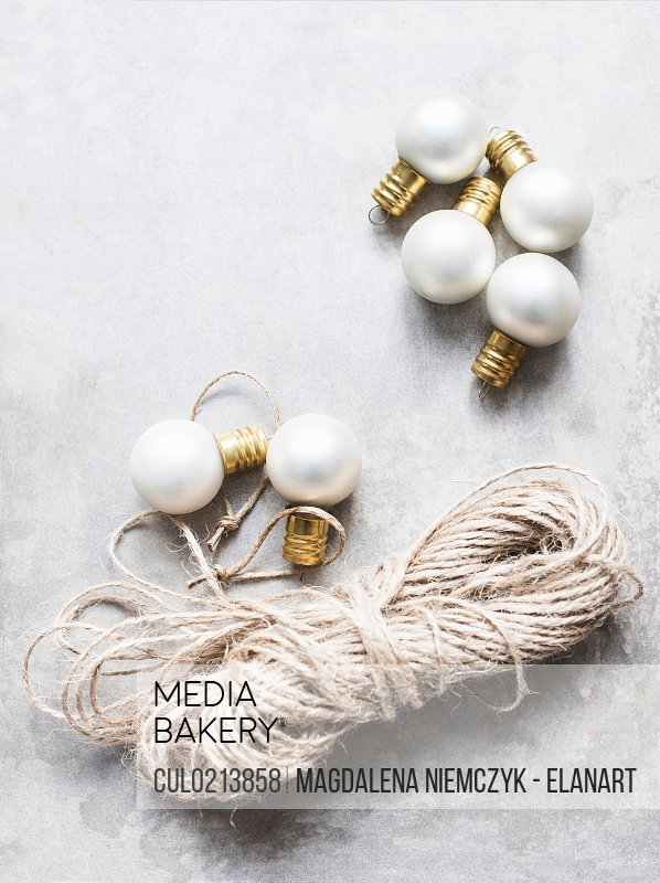 Overhead view of white Christmas baubles with string