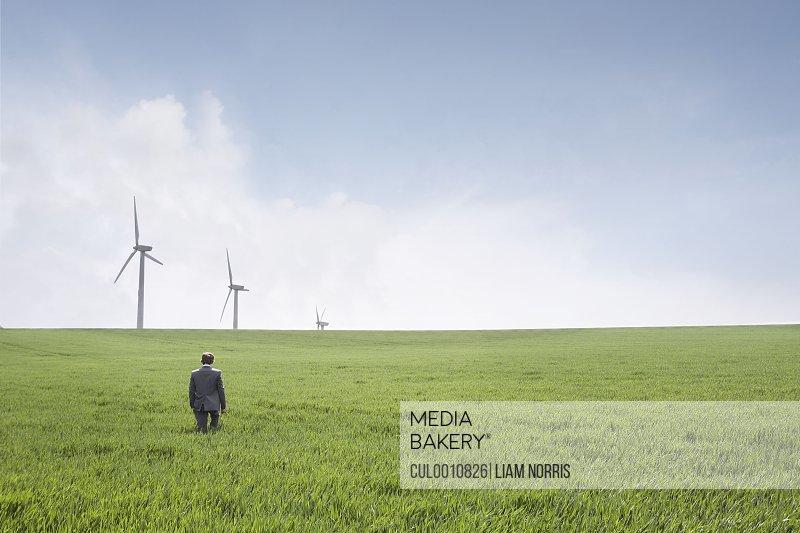 Man walking towards wind turbines
