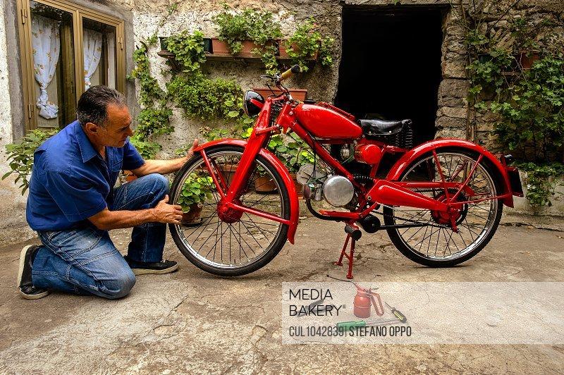 Mature man kneeling in courtyard, fixing red vintage motorcycle.