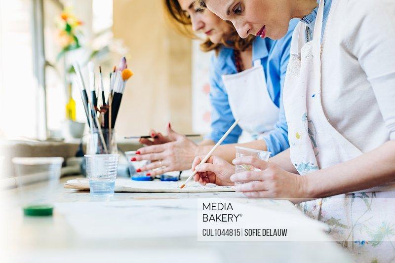 Two women painting in creative studio