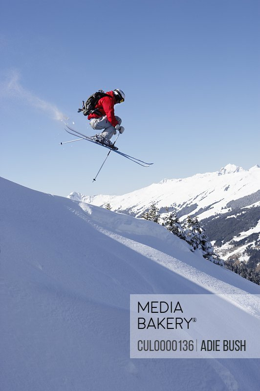 male skier jumping down slope