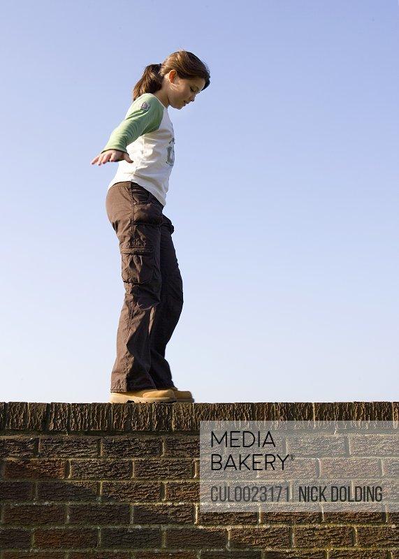 Girl balancing on wall