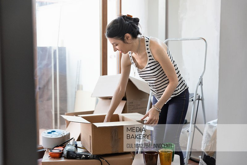 A woman putting items into a cardboard box.