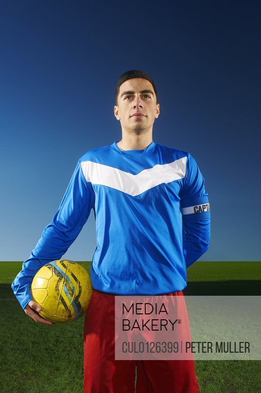Portrait of football team captain holding ball