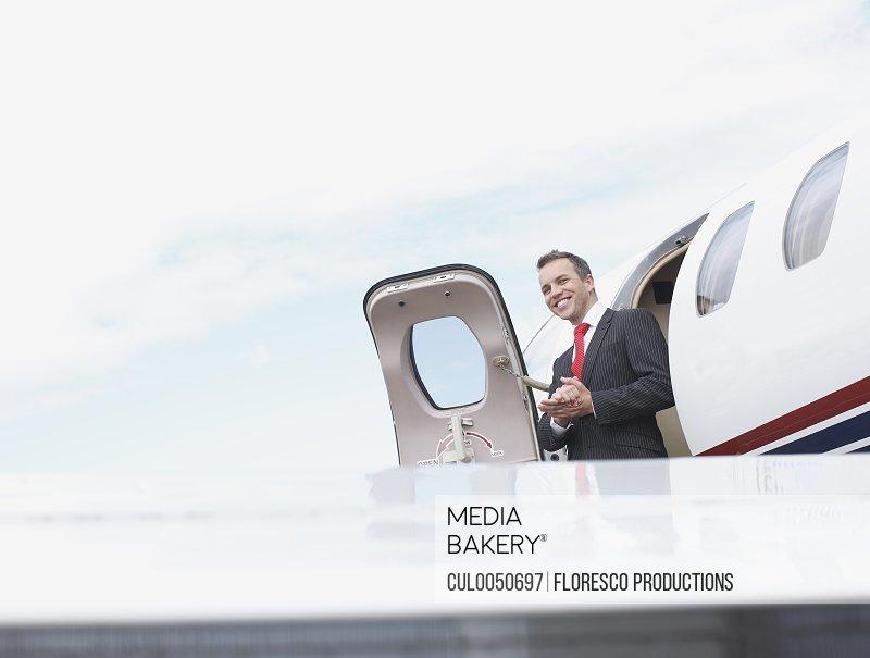 Businessman exiting corporate jet