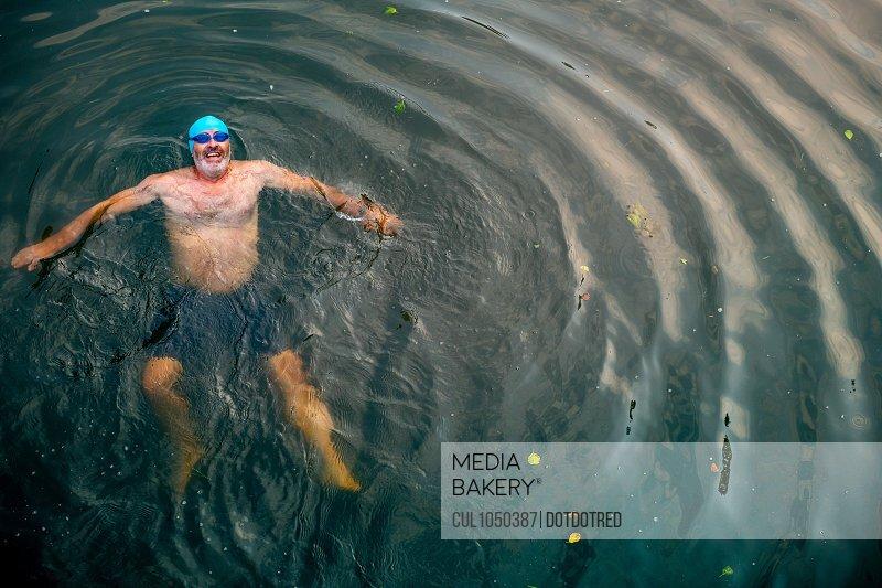 Man wild swimming in river, overhead view, River Wey, Surrey, UK