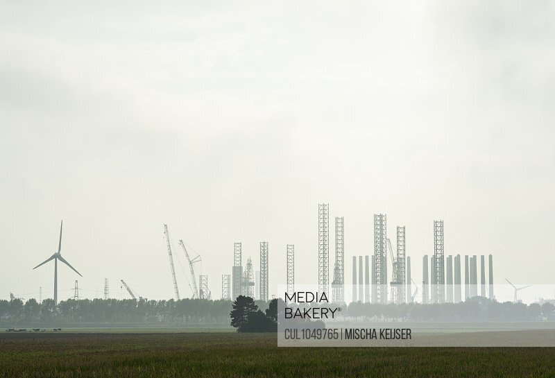 Foundations for offshore wind turbines yet to be constructed are stored besides disused oil rigs in the Vlissingen harbour, Lewedorp, Zeeland, The Netherlands