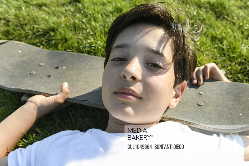 Boy with brown hair lying on grass, head resting on skateboard, looking at camera.