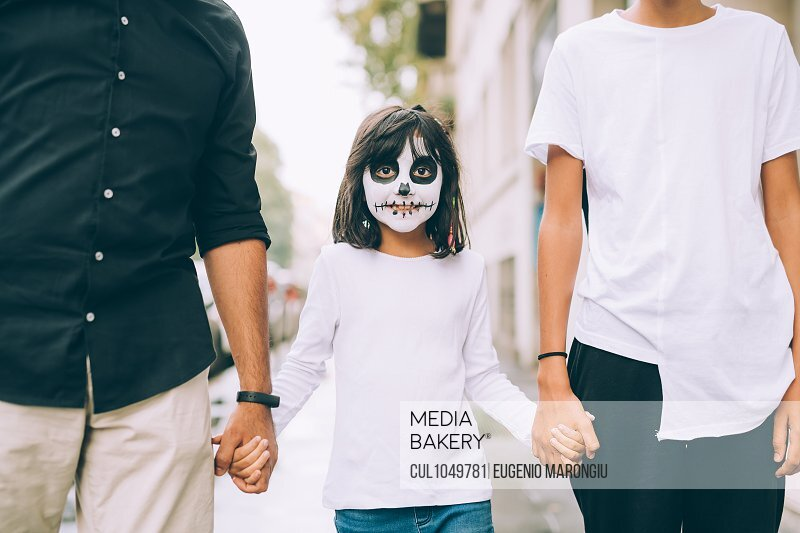 Girl with Halloween face paint, holding hands