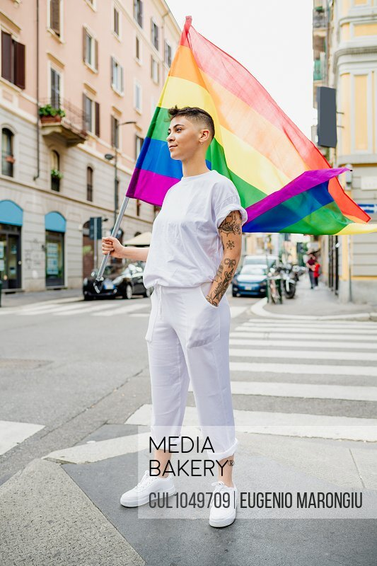 Young lesbian woman standing on a street, waving rainbow flag.