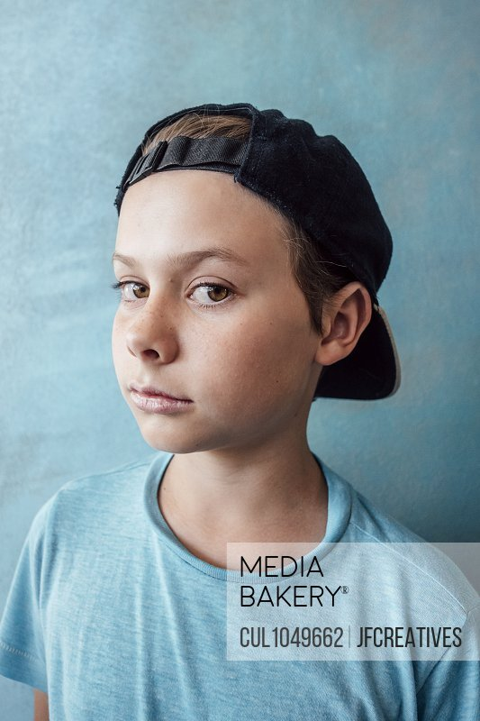 Portrait of boy wearing baseball cap, looking at camera, on blue background.