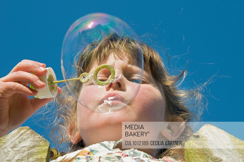 Close up of girl blowing bubbles