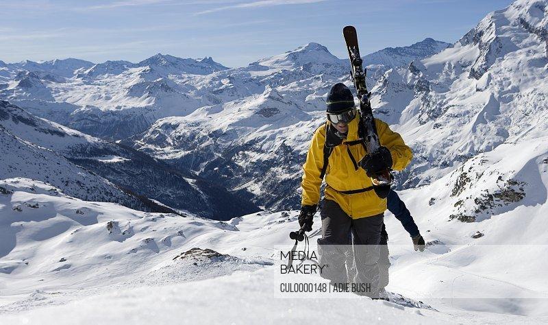 Two male skiers walking up mountain ridge carrying skis