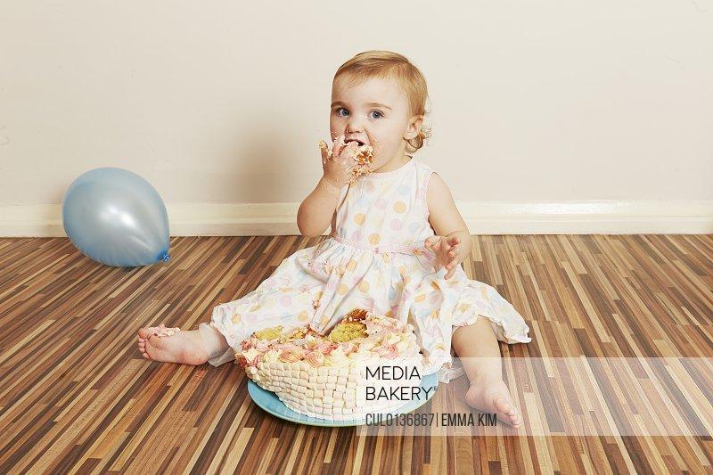 Toddler girl devouring birthday cake