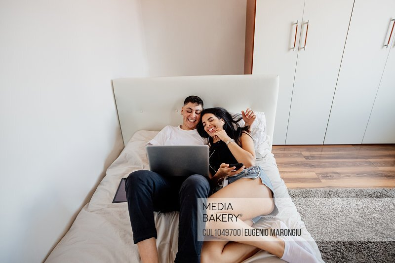 Young lesbian couple lying on a bed, looking at mobile phone and laptop.