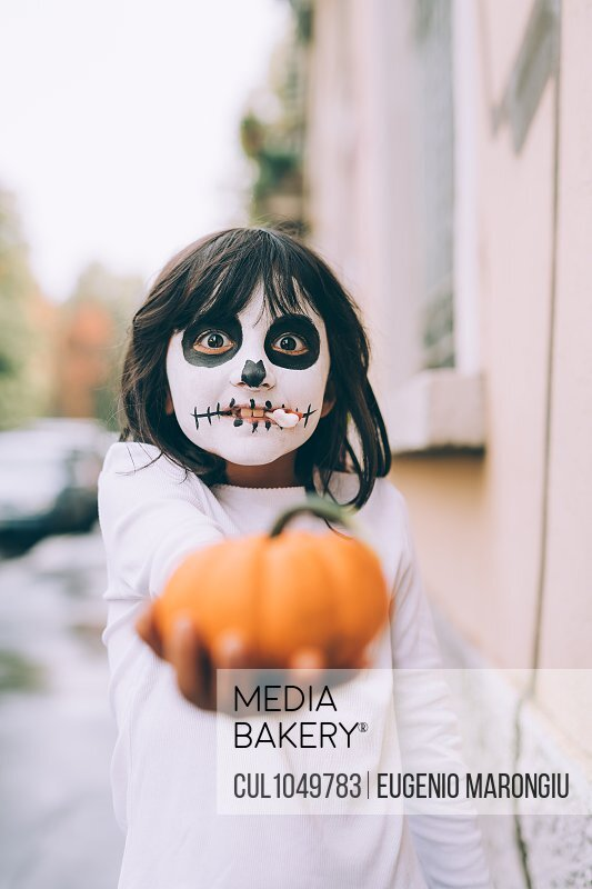 Girl at Halloween with face paint, holding out pumpkin