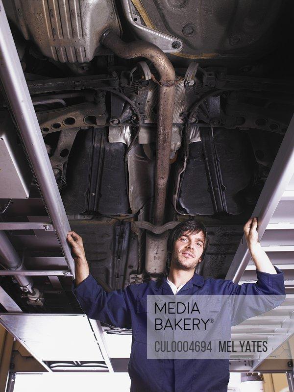 Mechanic standing under raised car